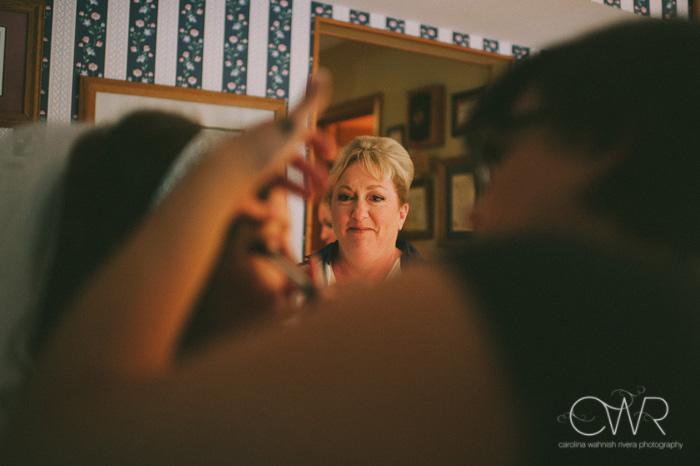 mom looking at bride getting makeup