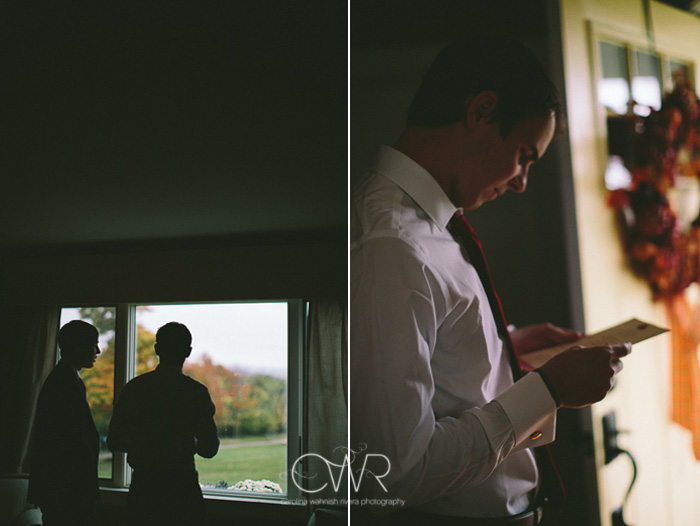 october wedding groom looking out window before ceremony with fall foliage