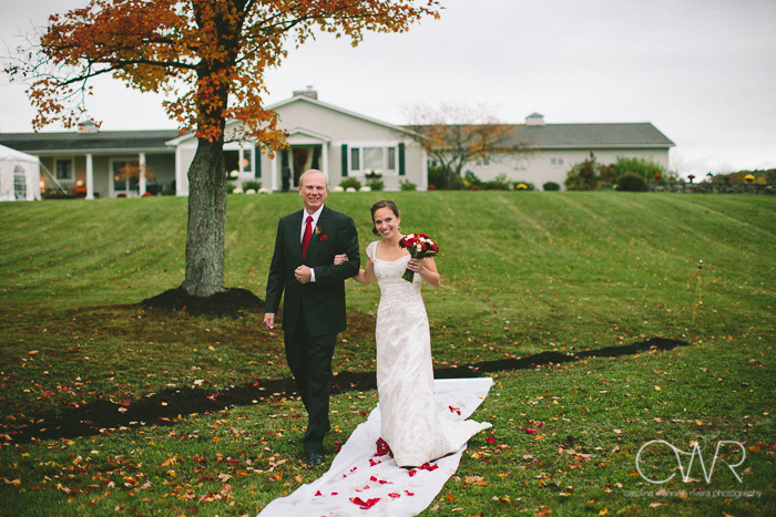 tented wedding in upstate ny on private residence as bride and father walk down