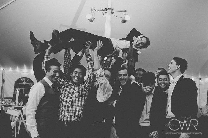 vintage wedding photographer captures fun photo in black and white of groom and his friends