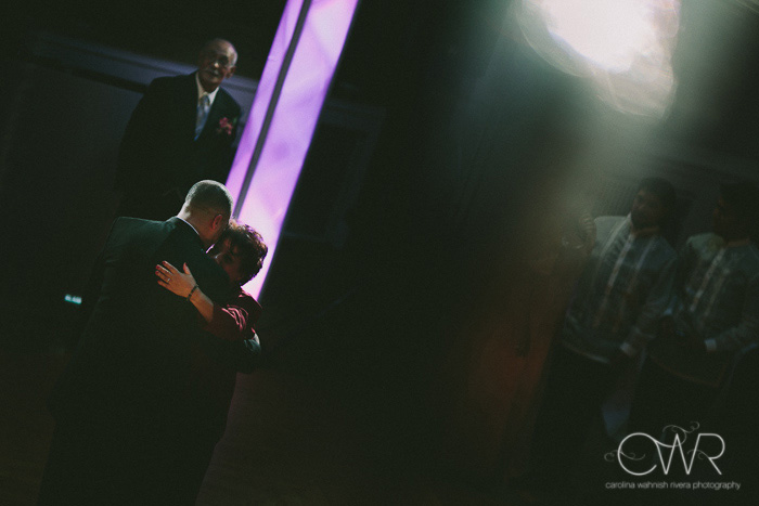 candid wedding photography dramatic lighting dance between groom and mother