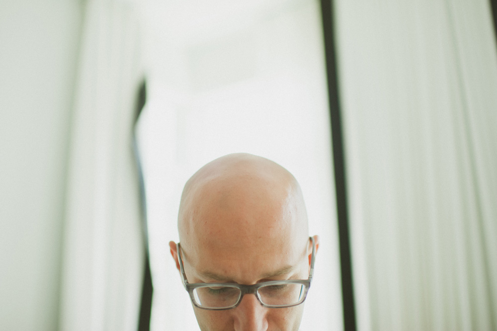 beach wedding photographer simple portrait of groom with bald head by window