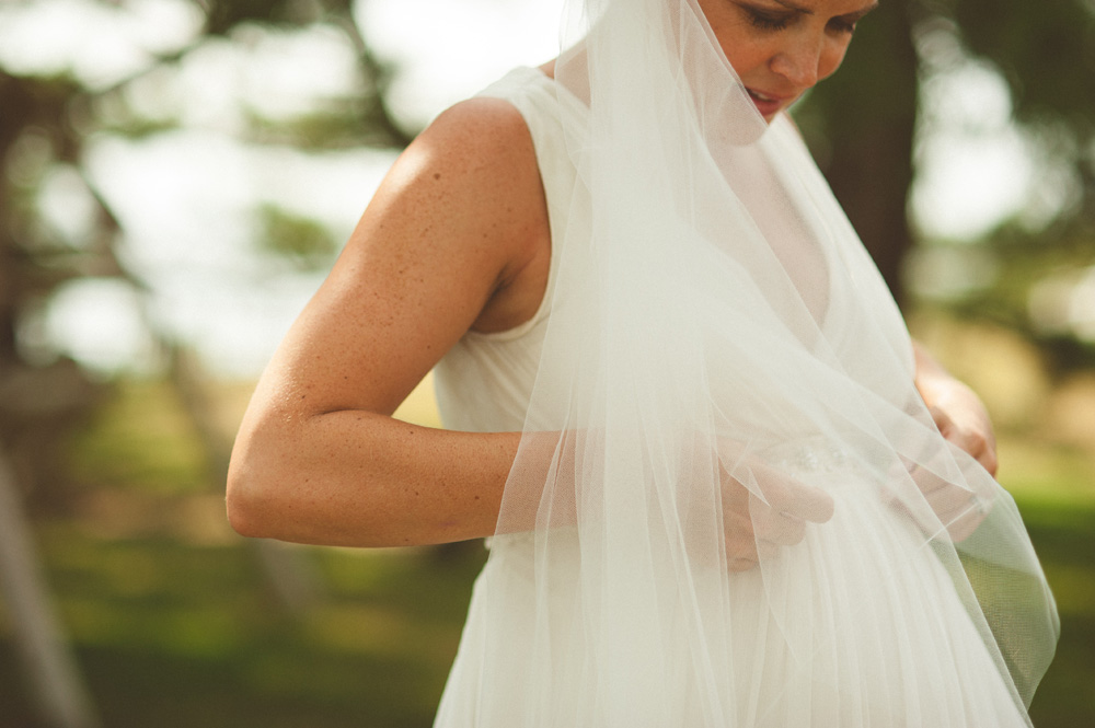 beach wedding photos, intimate moment of pregnant bride looking down at her belly