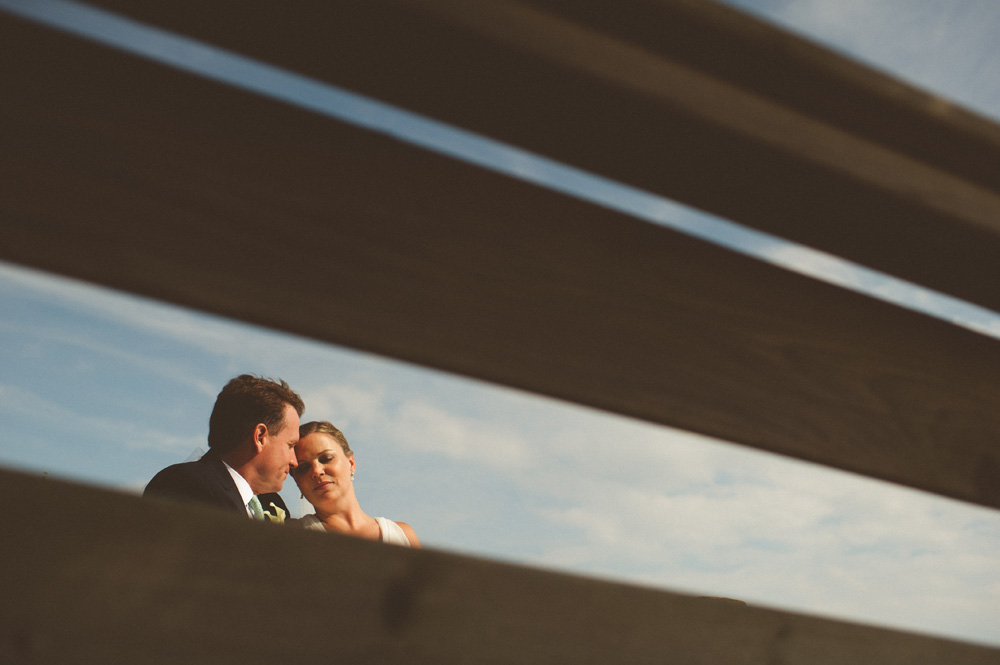 beach wedding photos creative portrait of bride and groom shot through bench during new york wedding