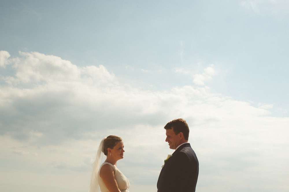 beach wedding photos of bride and groom with clear sky