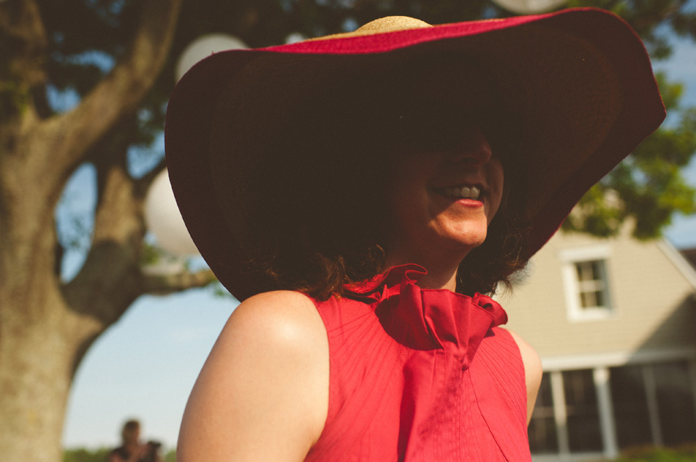 destination wedding photographer, guest with bright red large hat and red lipstick smiling