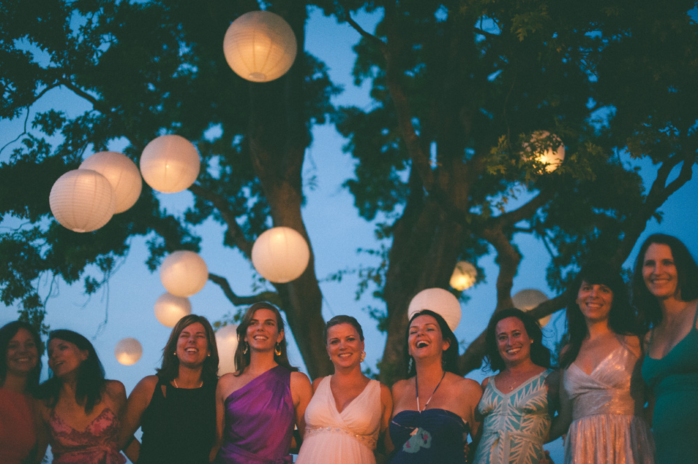 outdoor wedding reception paper lanterns lit up at night with group portrait