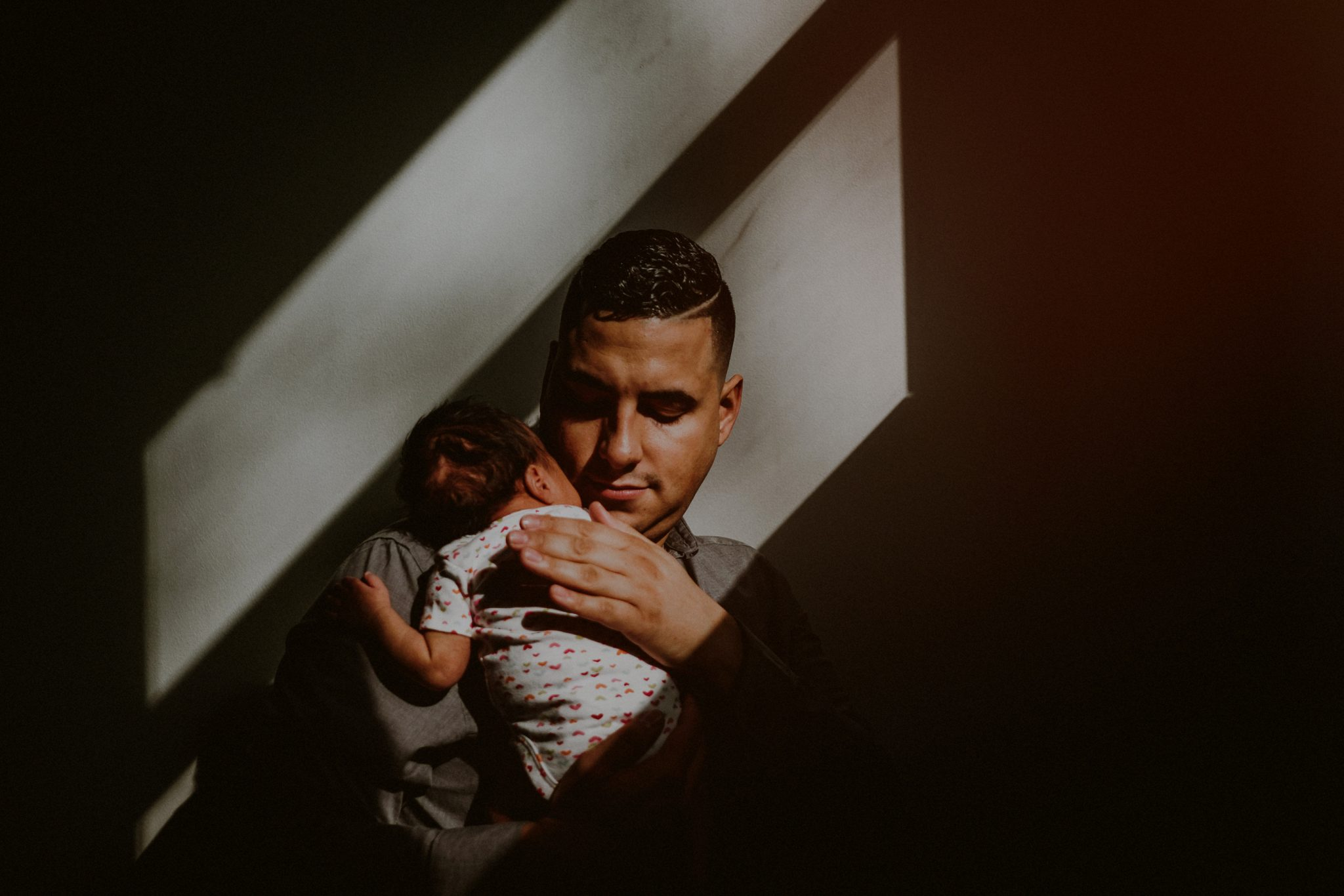 father tenderly holding baby in natural window light