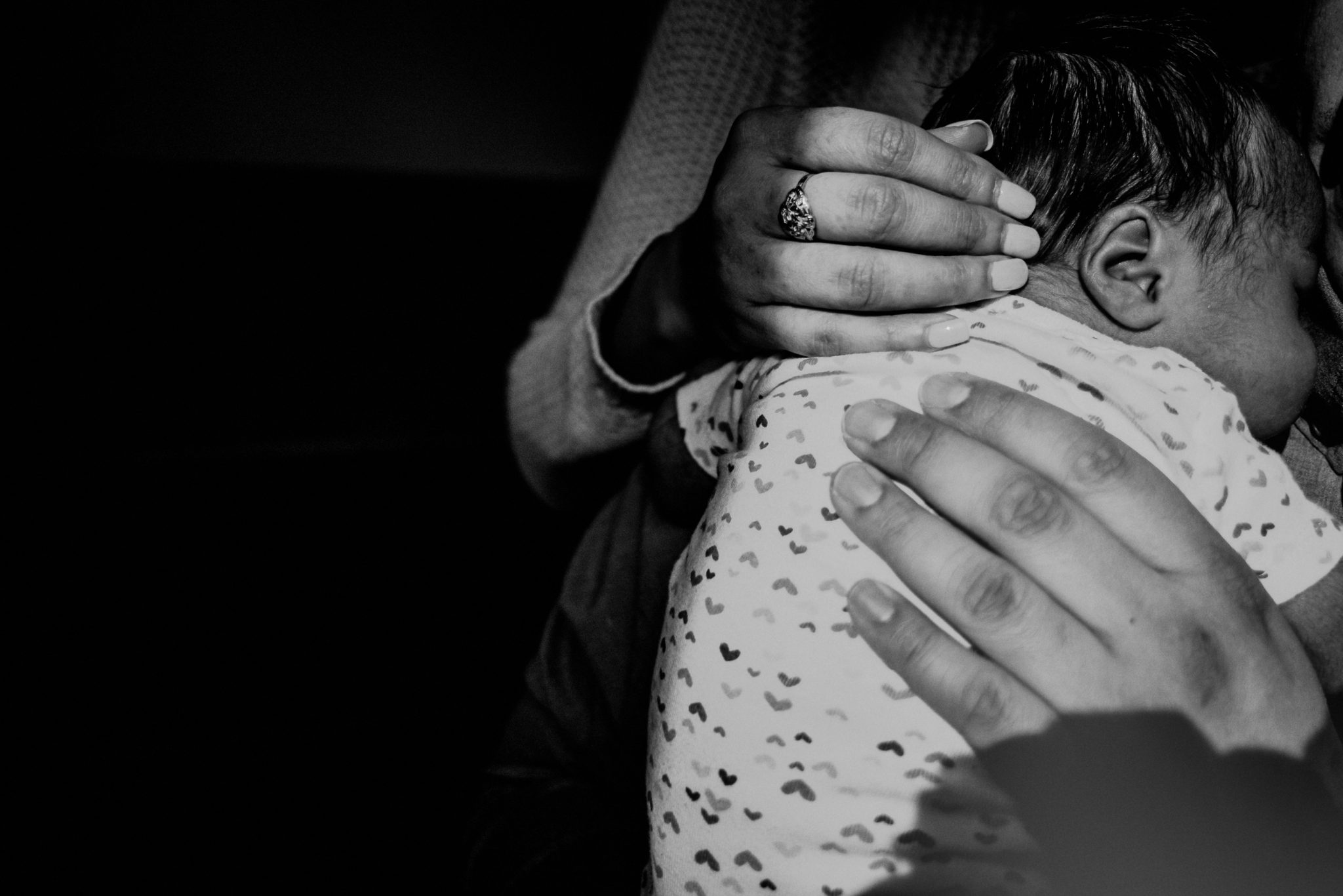 closeup of mother and father's hands on newborn baby, black and white photo