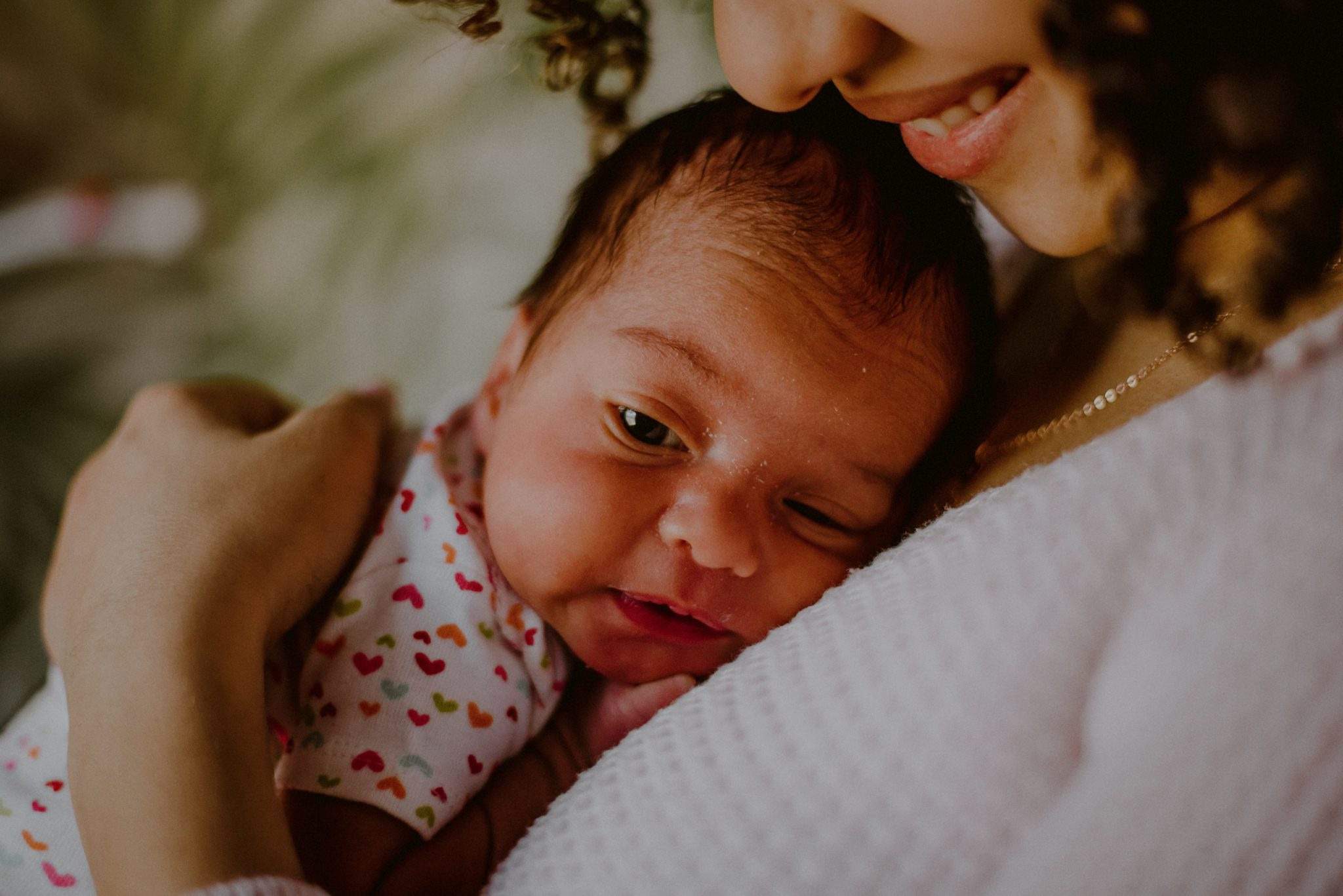 baby with eyes open on mother's chest while mom smiles