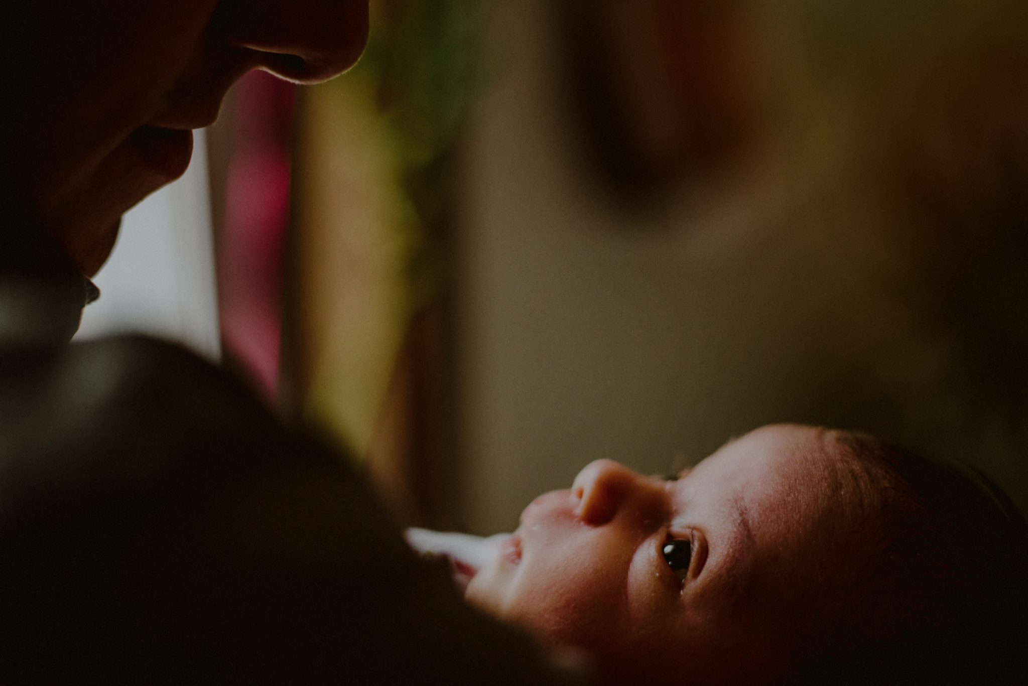 newborn baby tenderly looking up at father