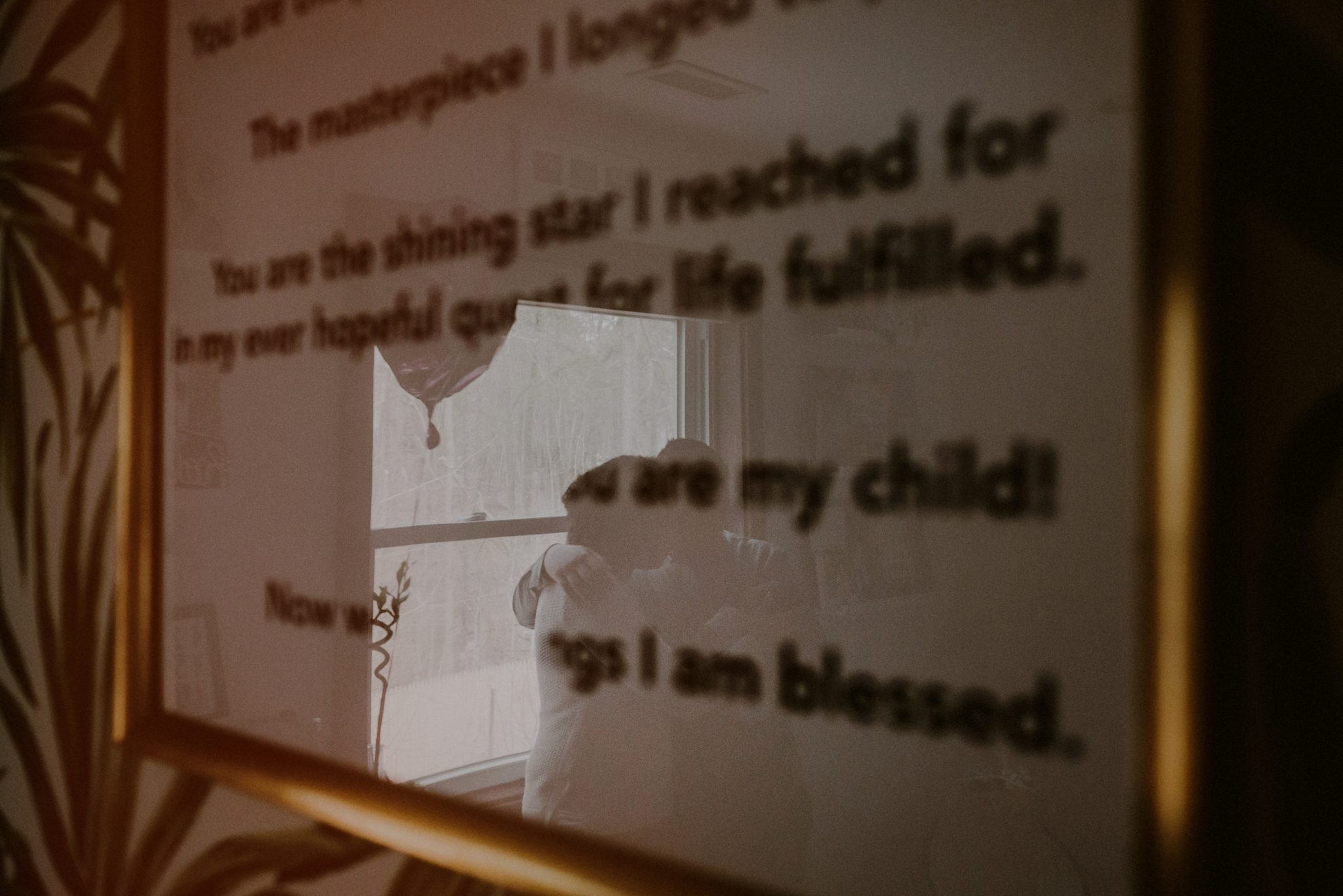 reflection of family portrait seen through biblical quote on framed print on wall
