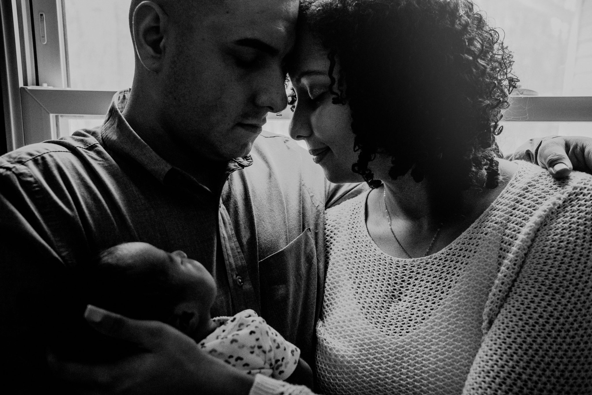 black and white emotional family portrait with newborn