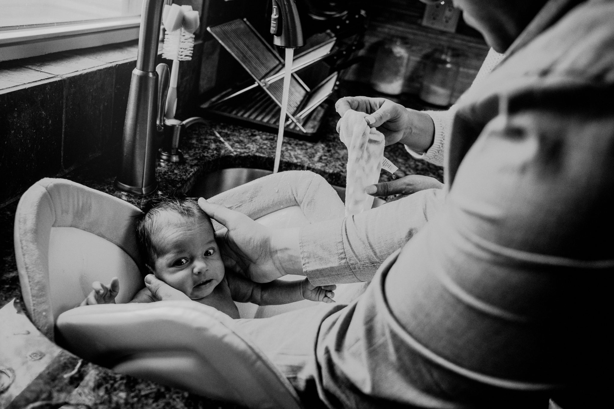 baby's first bath expression in black and white image