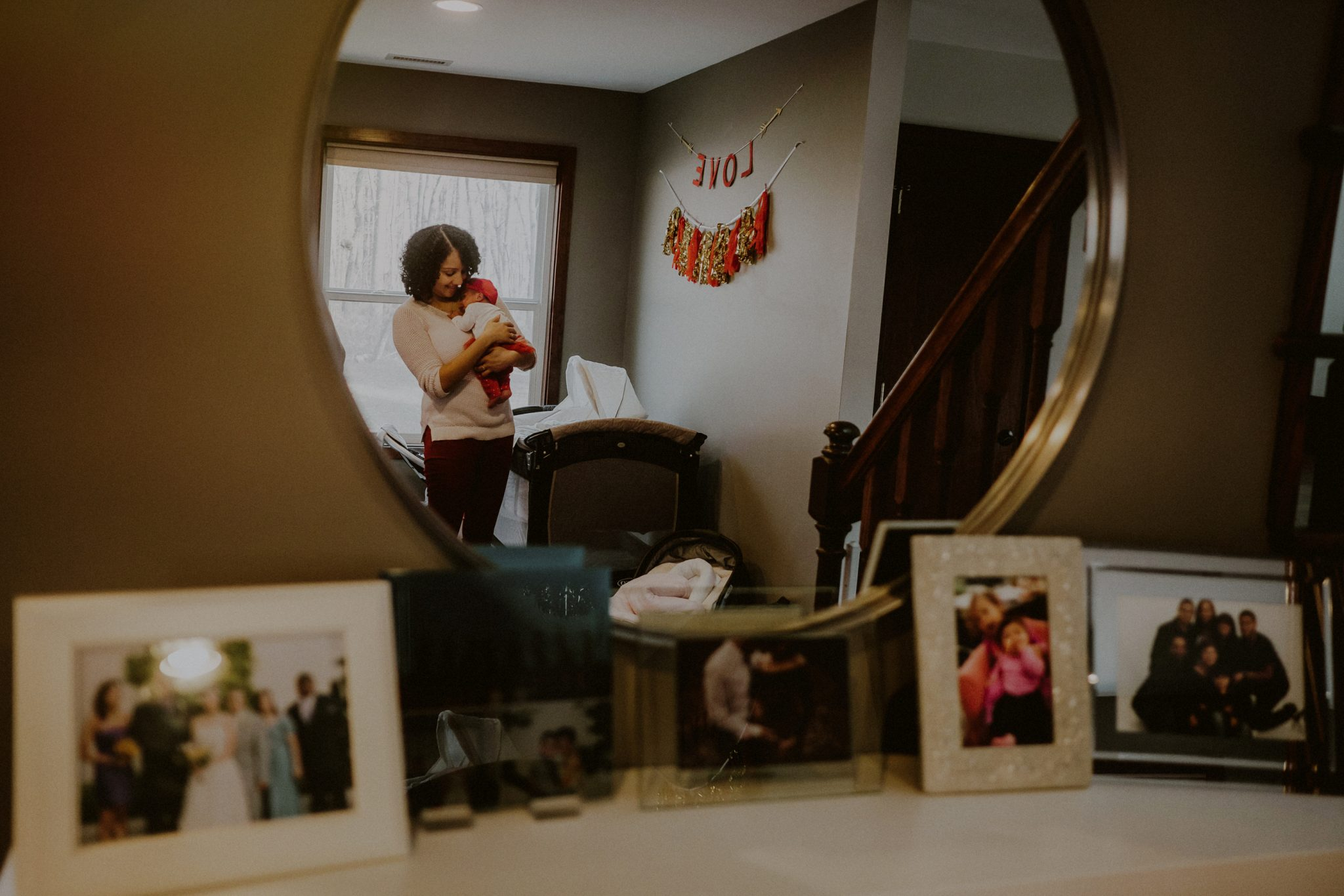 reflection of mother holding child in mirror, juxtaposed by printed family photos on counter