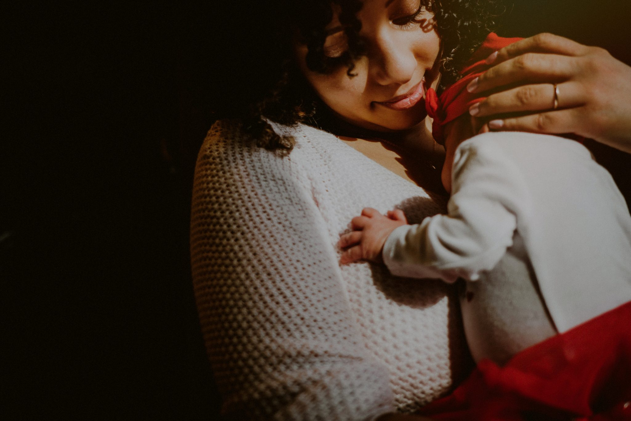 emotional photo of mother holding daughter in harsh light by window
