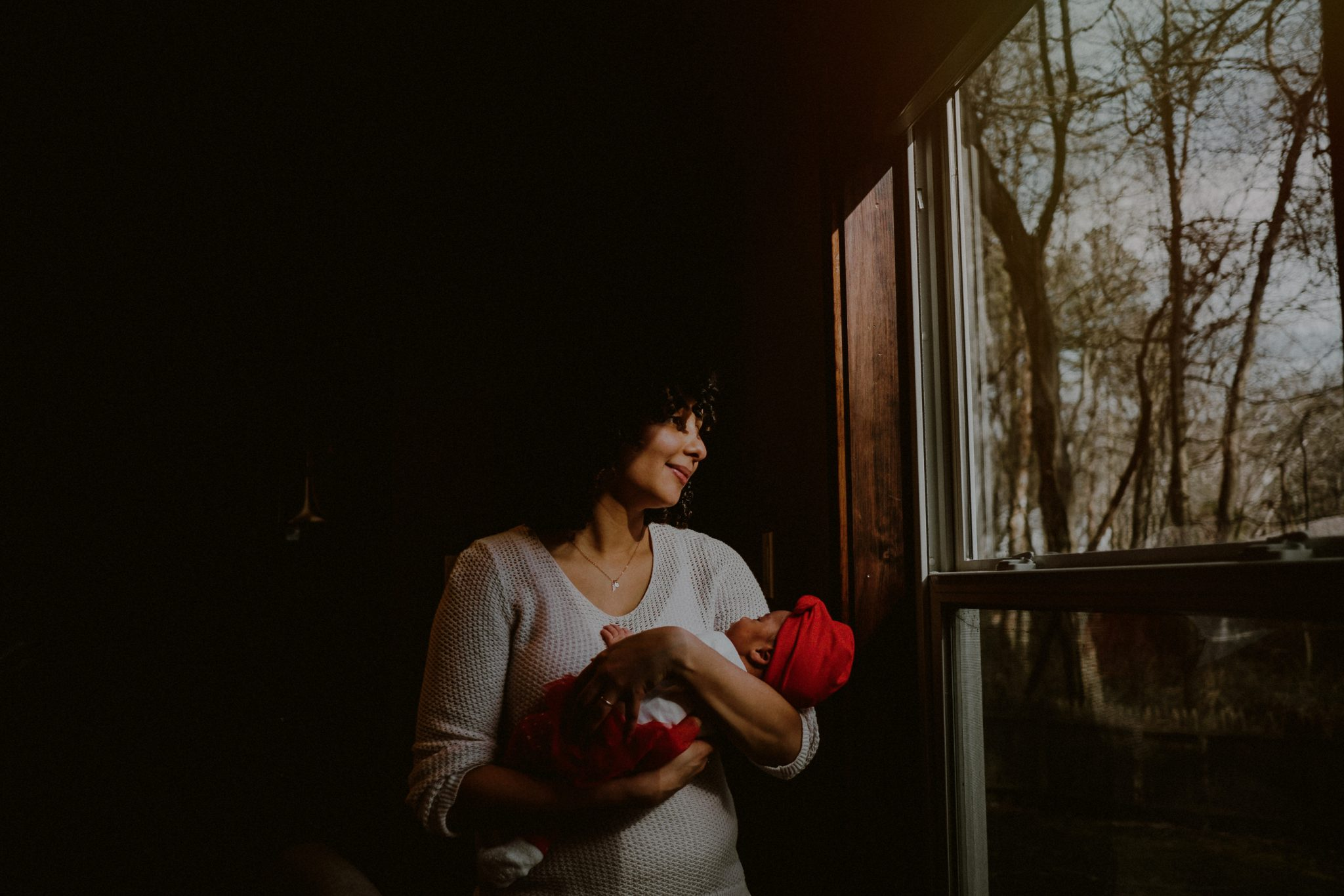 mother looking out window holding baby