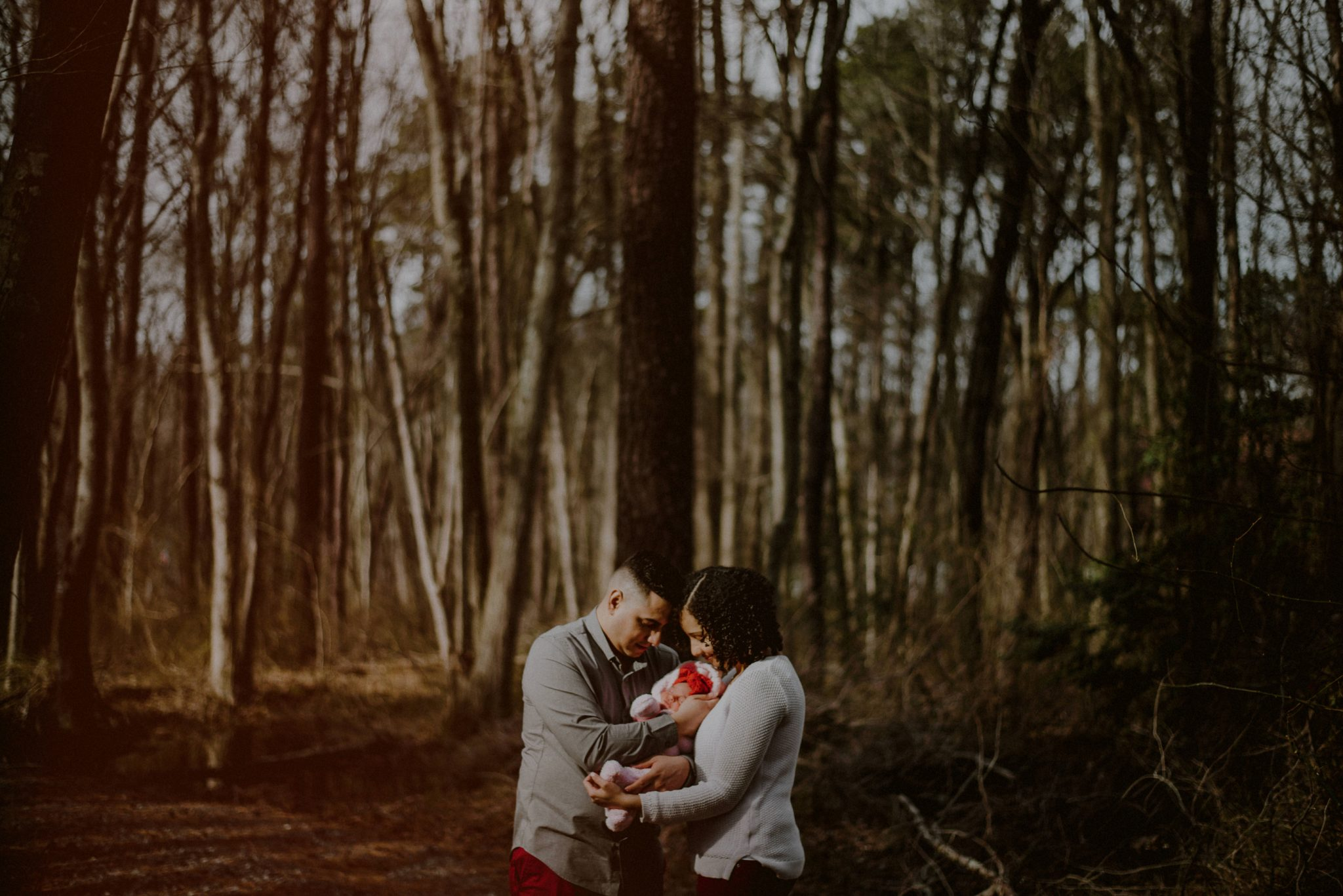 rustic outdoor family portrait in the woods with newborn surrounded by bare winter trees
