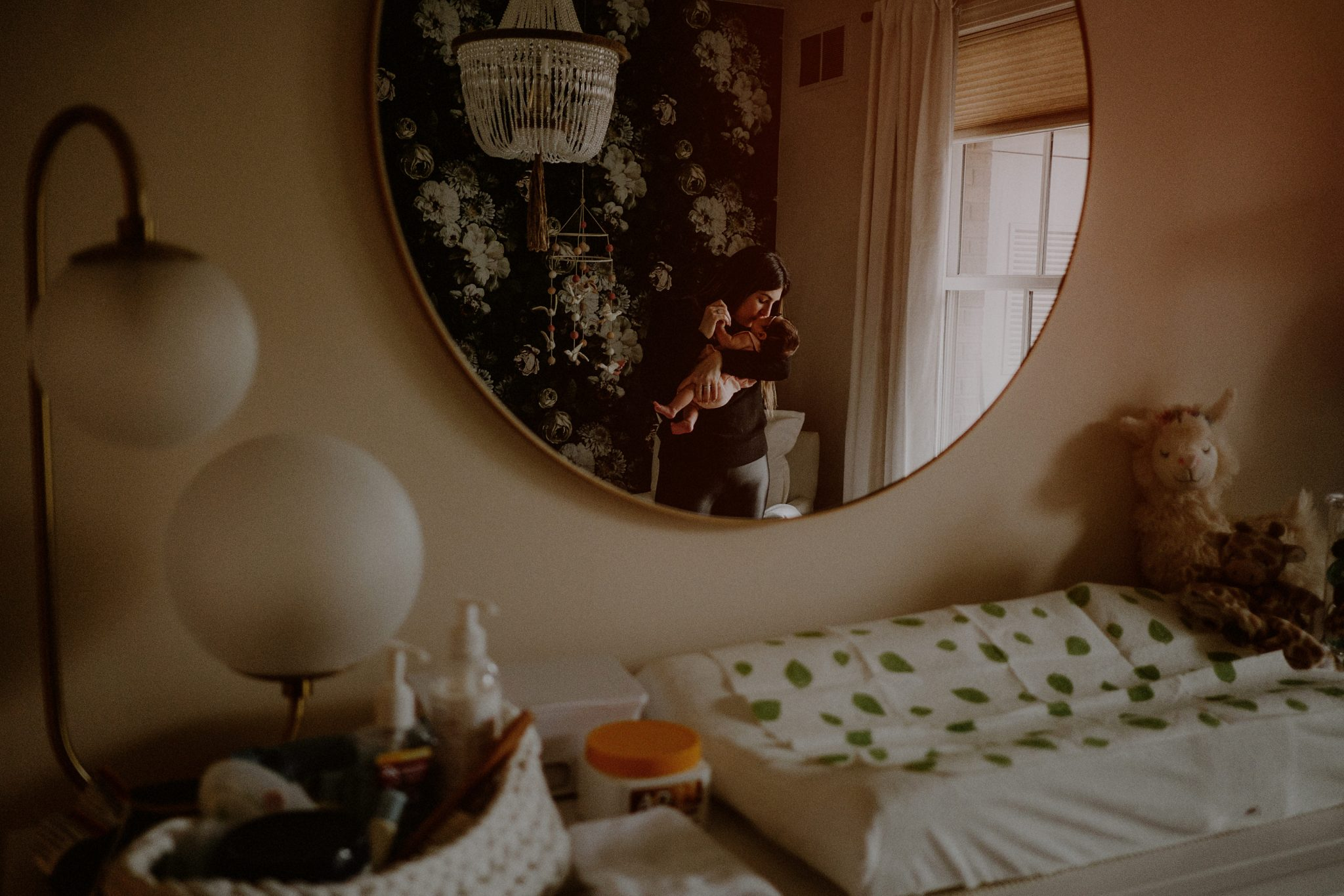 mother holding baby in reflection of mirror in baby's room