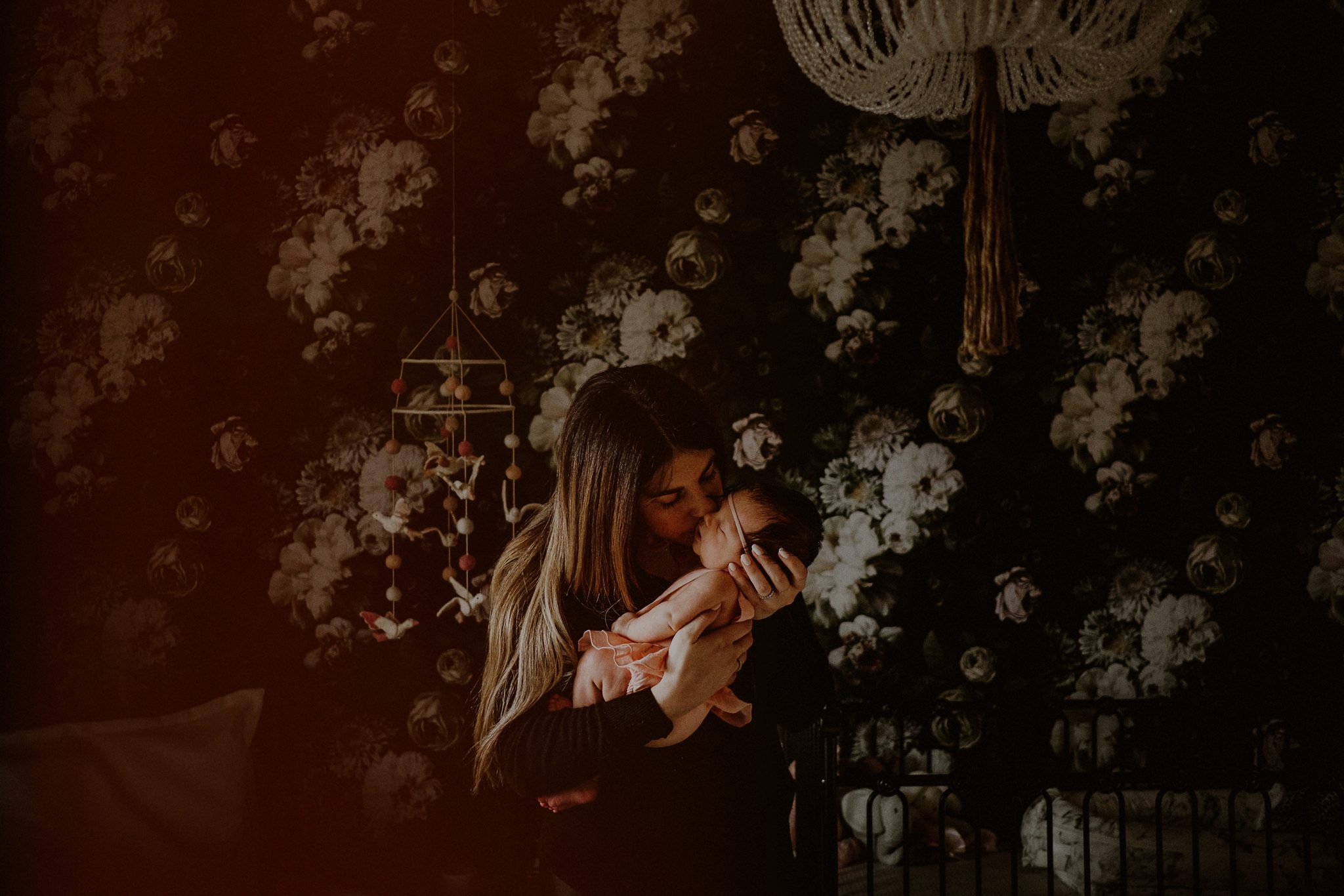 mother kissing baby in her arms in front of dark flowered wallpaper of bedroom