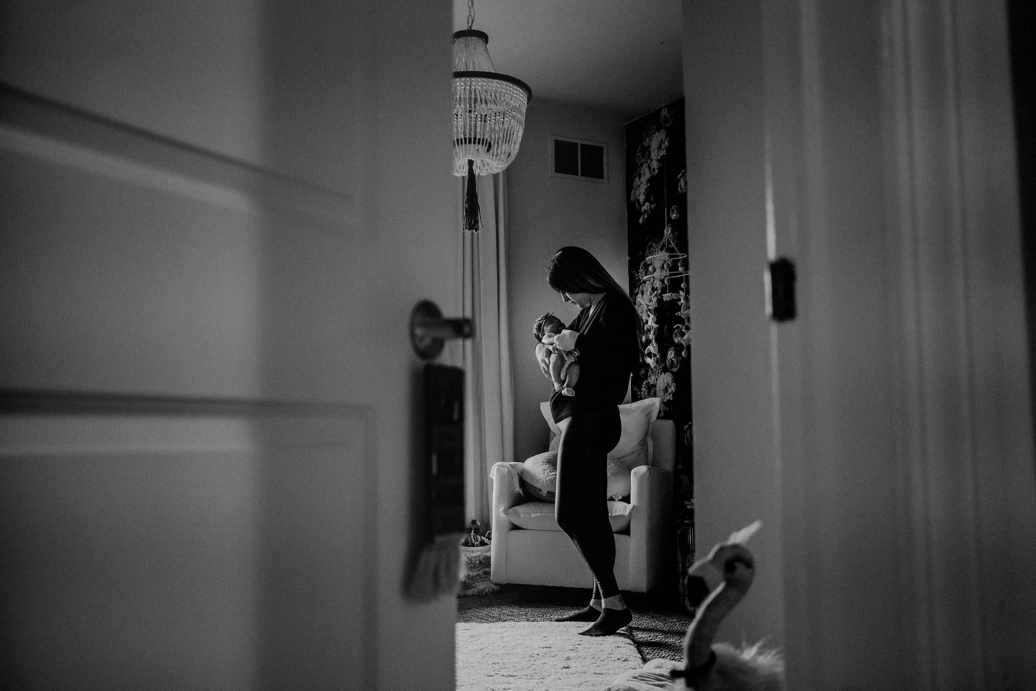 voyeur perspective of mother holding baby through crack in door of bedroom