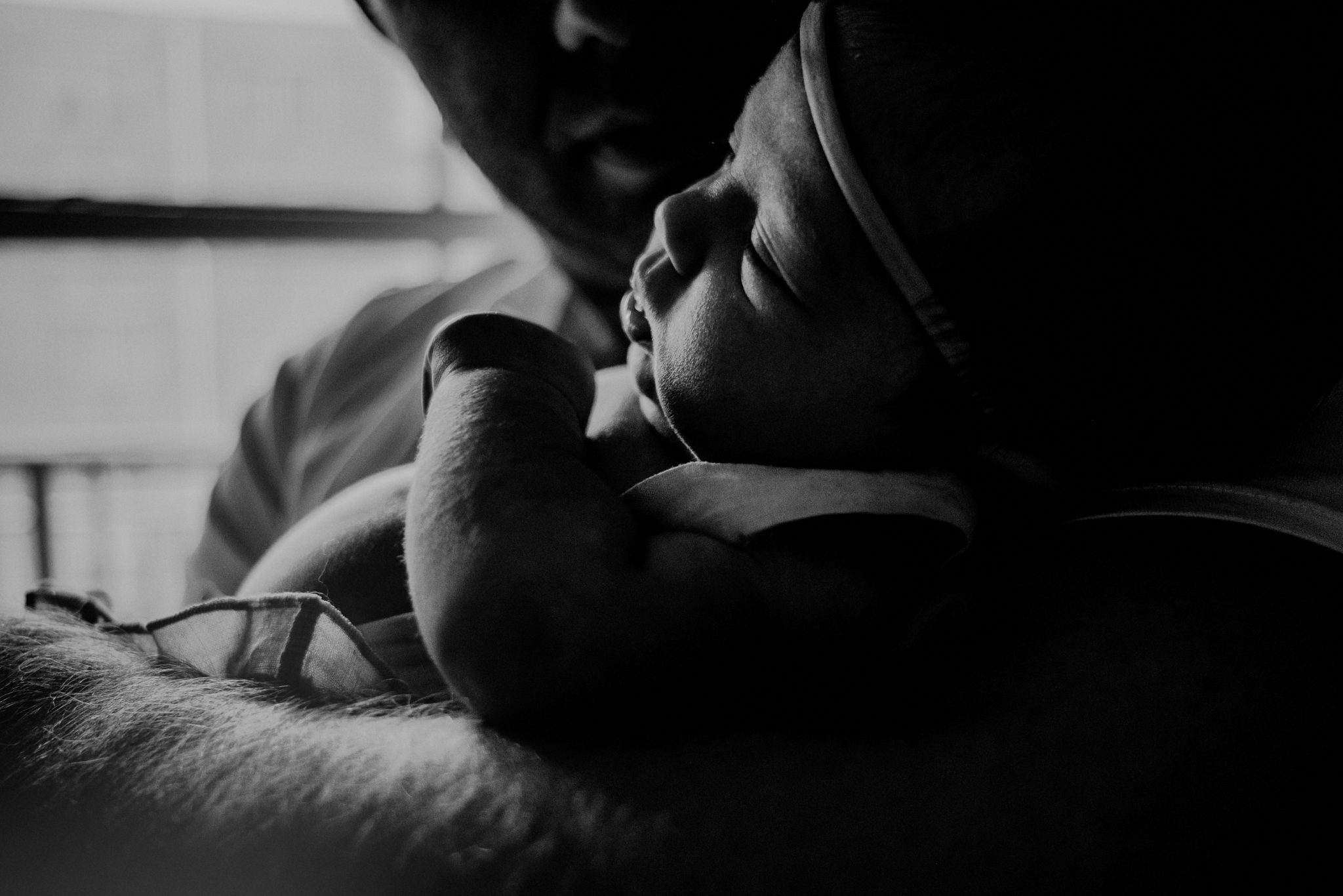 father's arm in foreground of black and white image holding baby