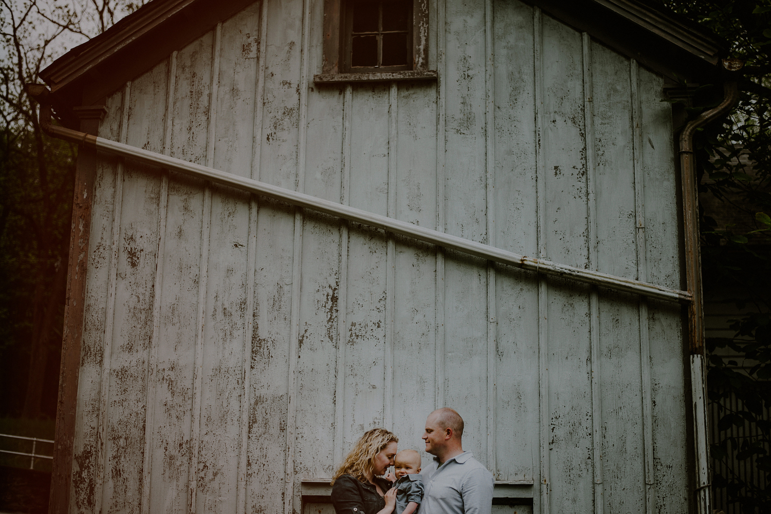 creative family photo posed in front of barn in NJ