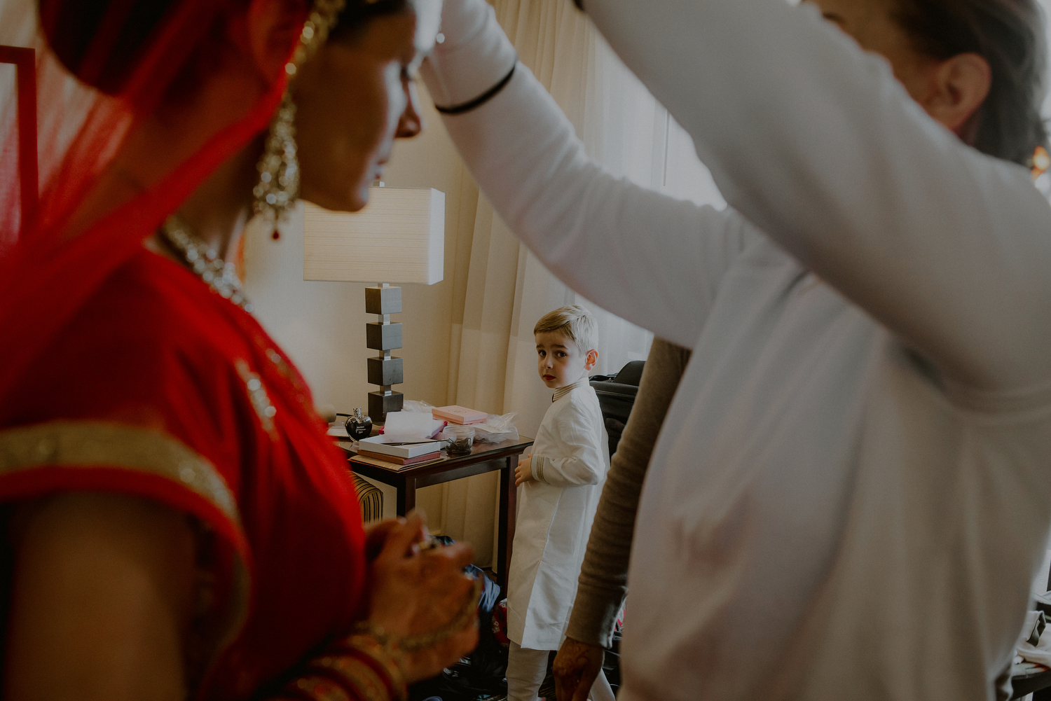 little boy looking on as indian bride gets dressed