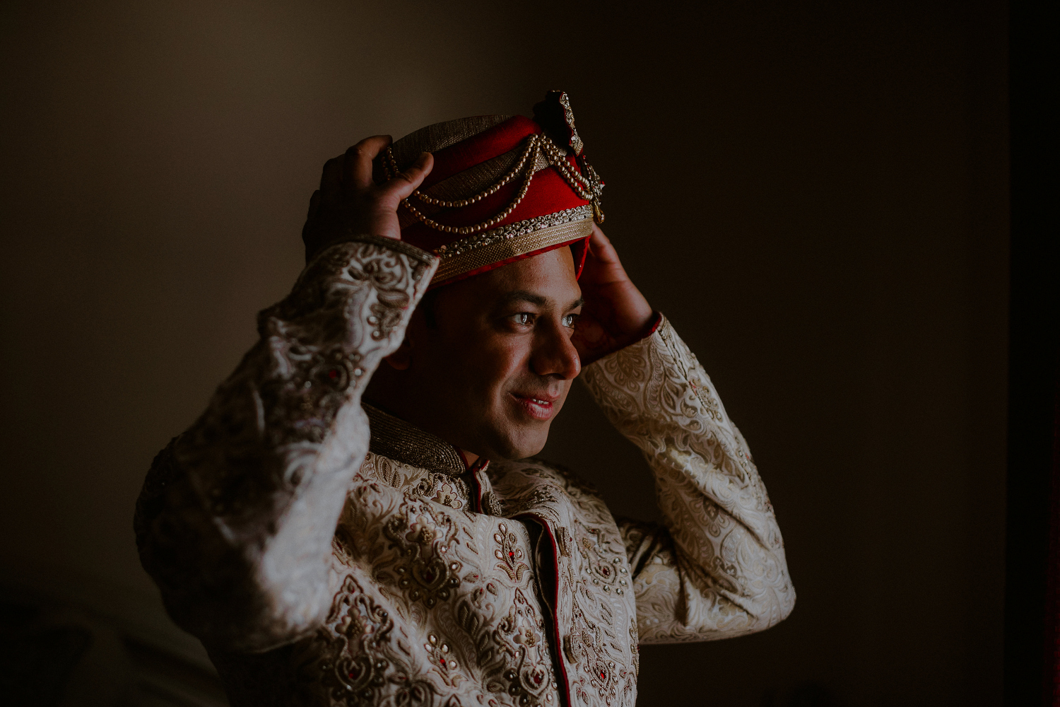 indian groom putting on turban and other indian groom attire
