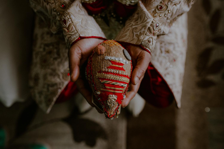 groom holds symbolic indian wedding ritual