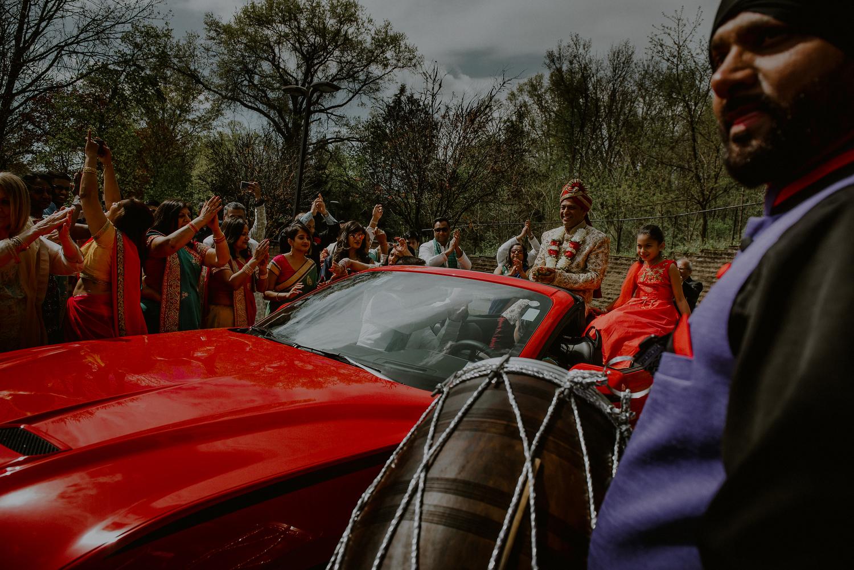indian wedding photos of groom arriving in red corvette to baraat