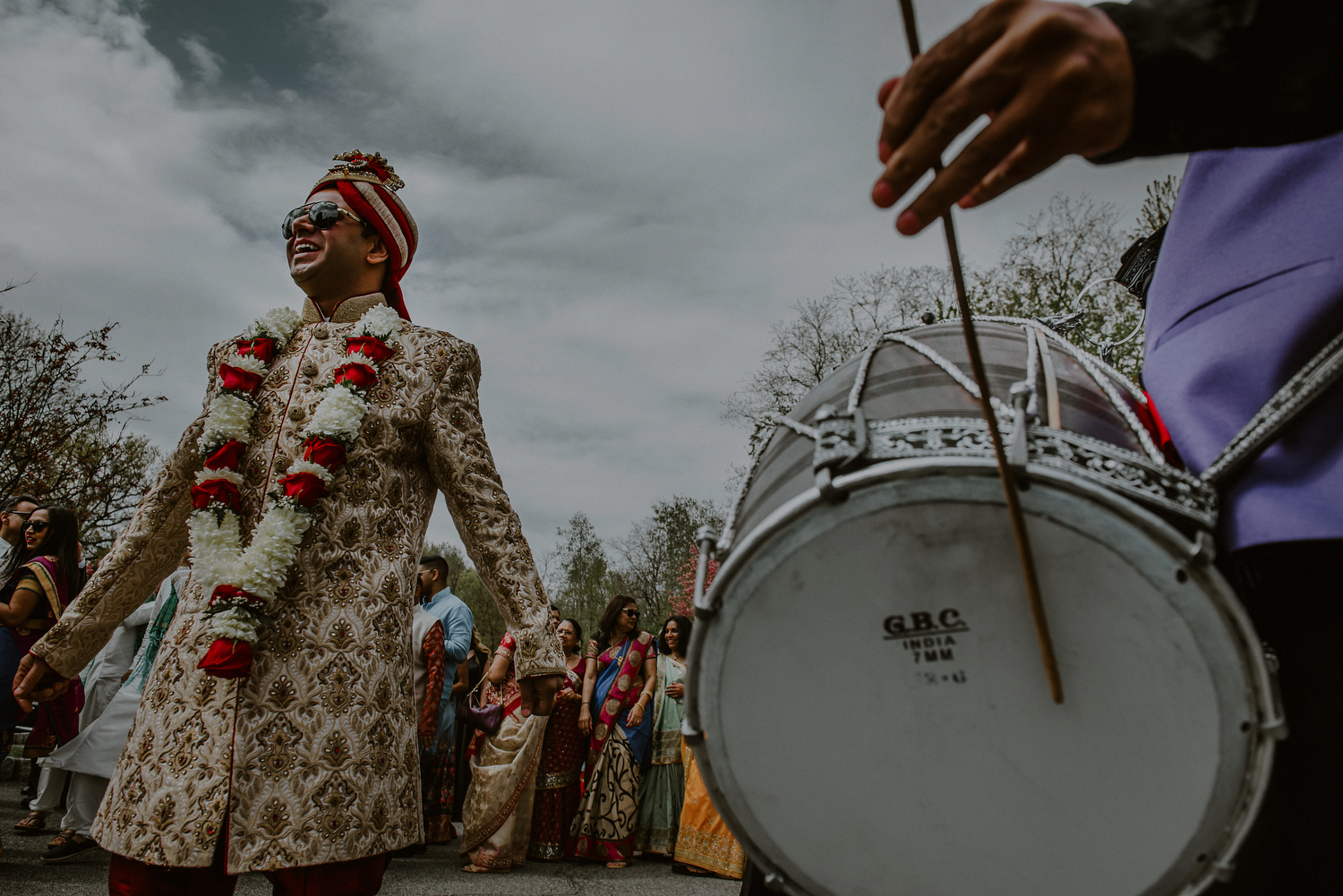 groom dances next to drums in baraat ceremony