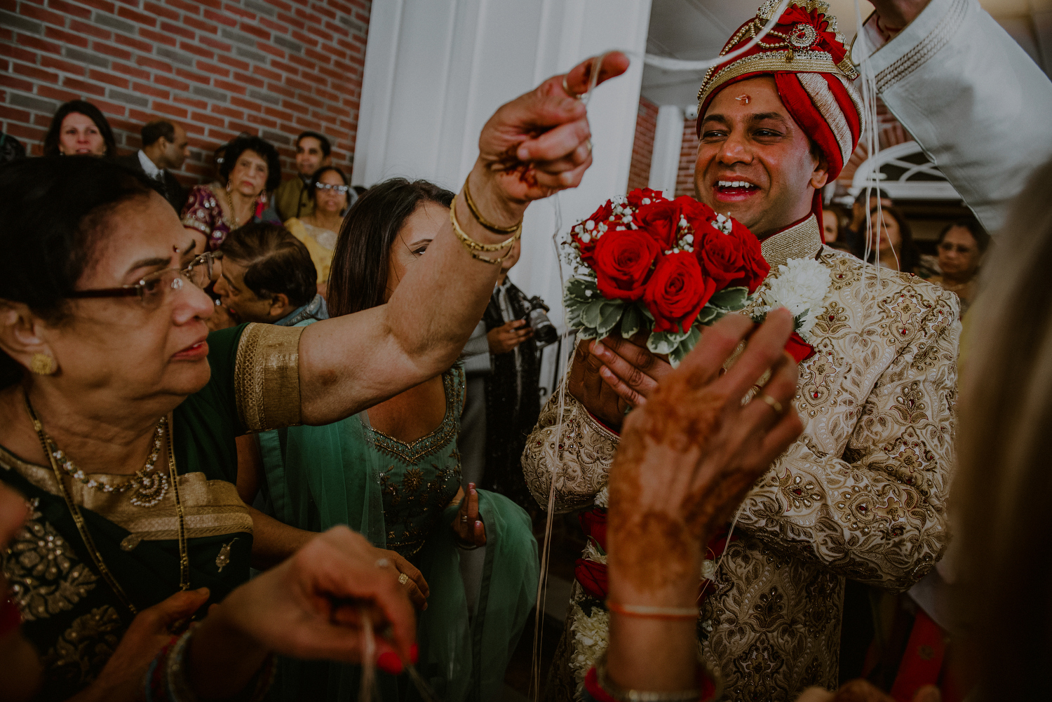 groom enjoys indian wedding rituals after baraat