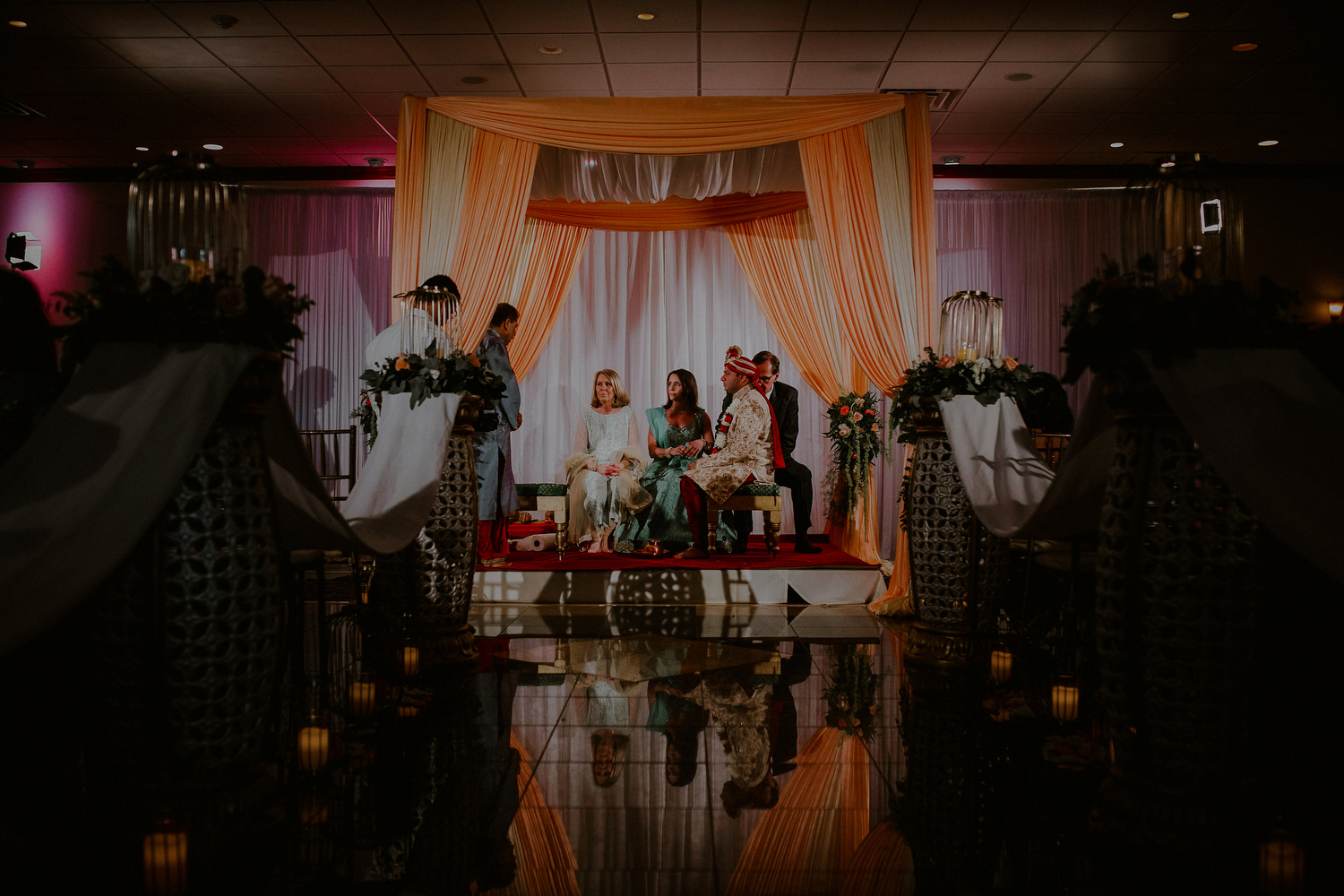 groom and parents under mandap in indian wedding photos