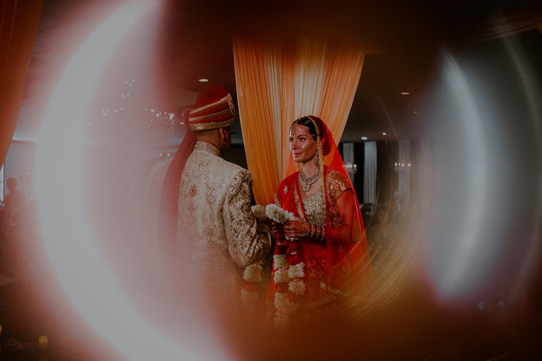 couple exchanges jai mala flower garland during wedding ceremony