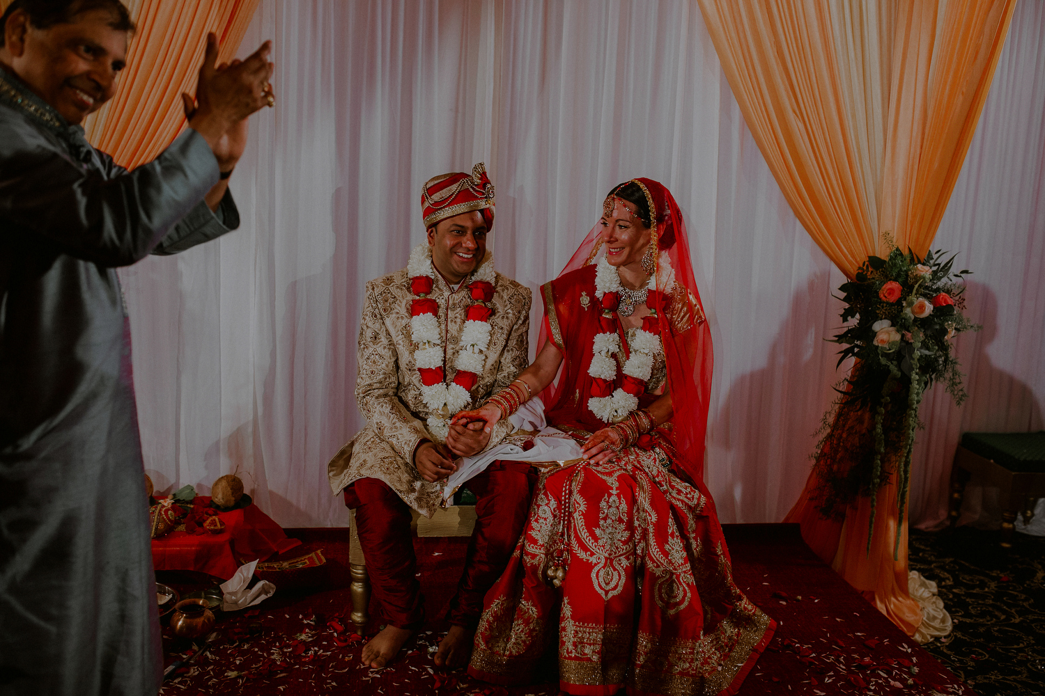 indian bride and groom marry under the mandap