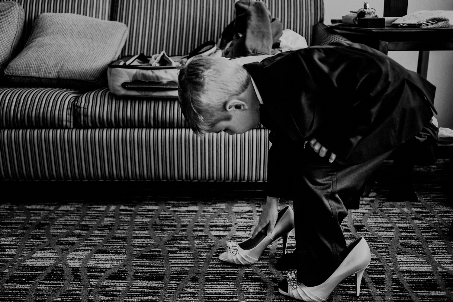 boy playing with bride's wedding shoes
