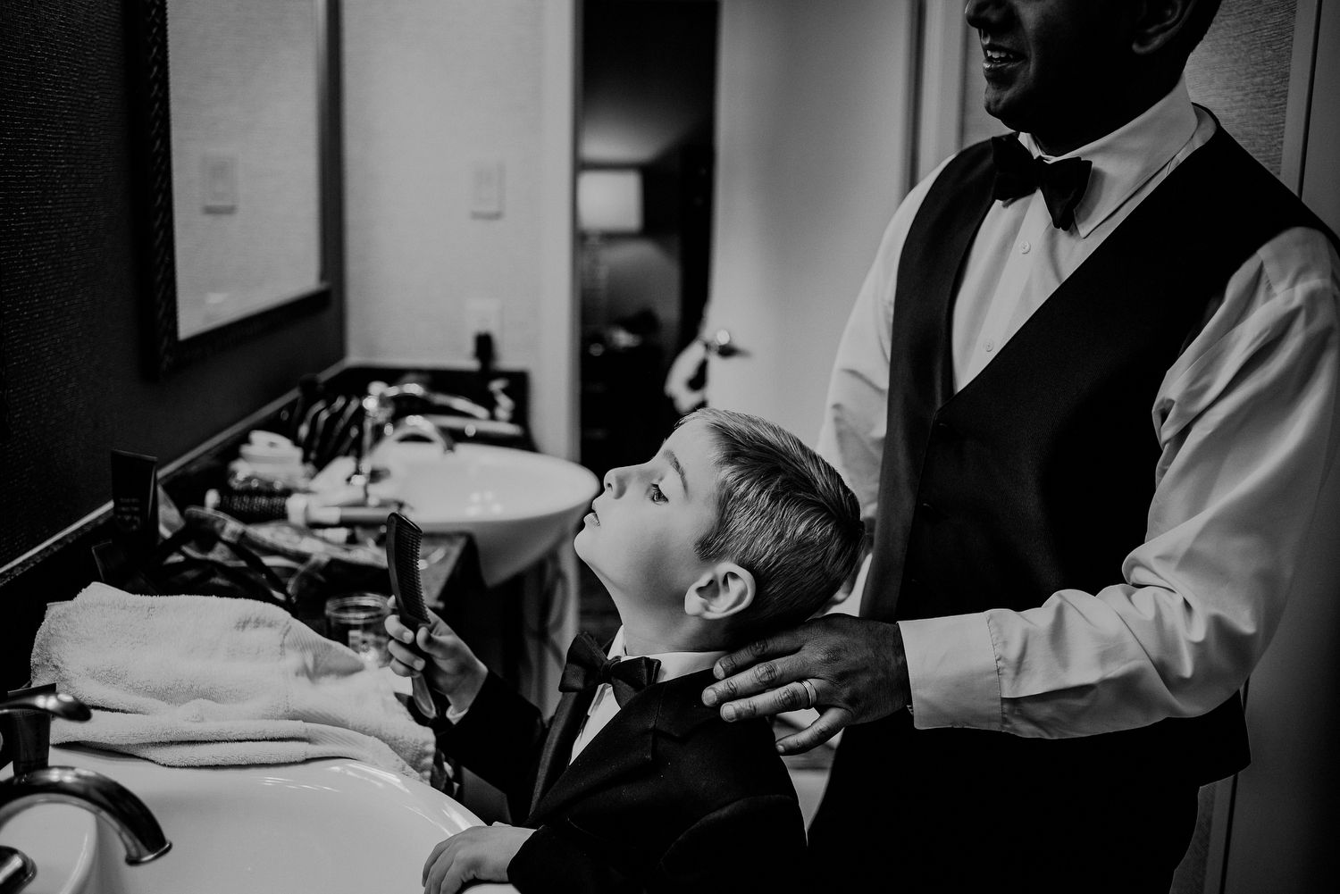 groom helps son get changed during wedding