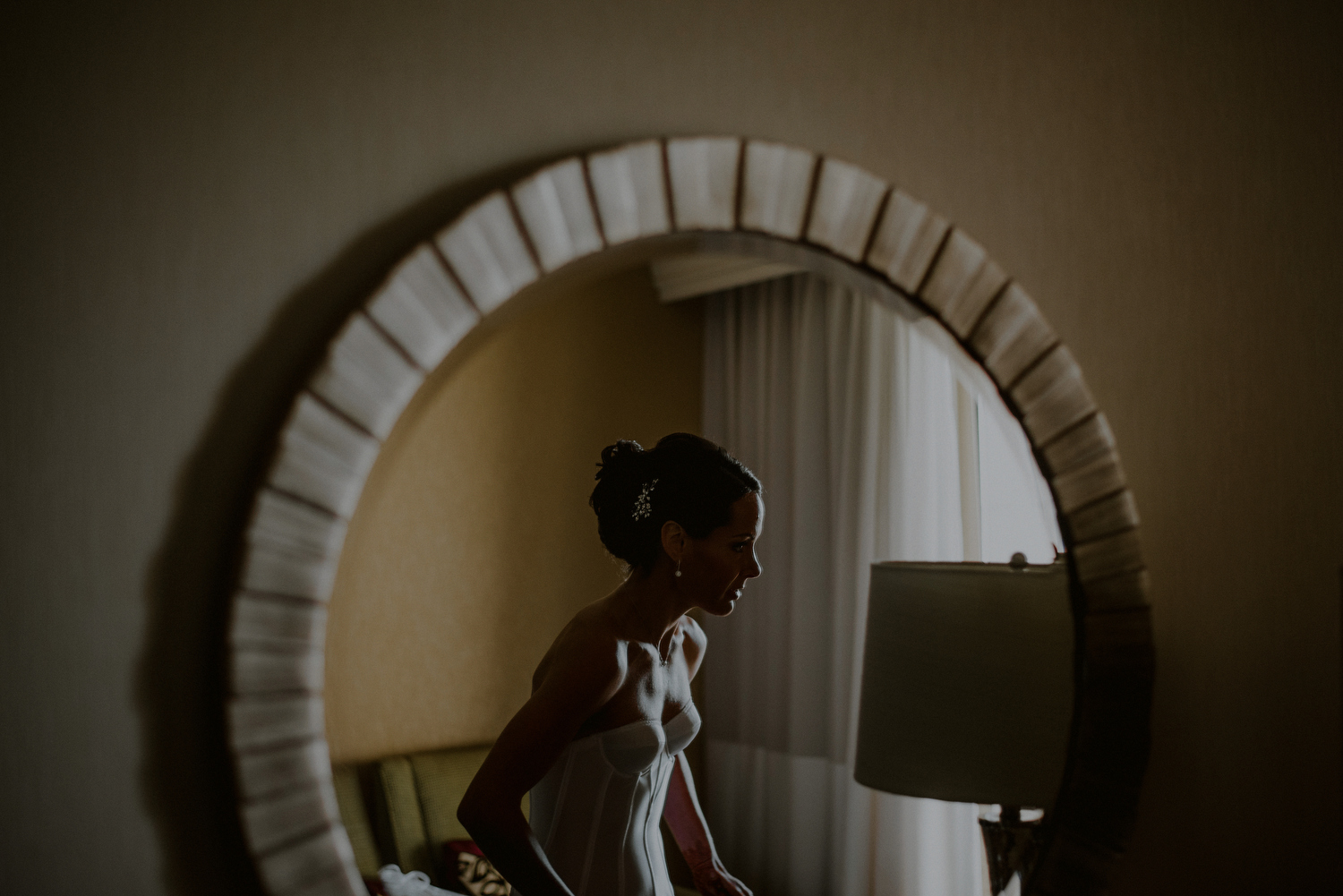 bride getting ready in reflection of mirror of hotel room