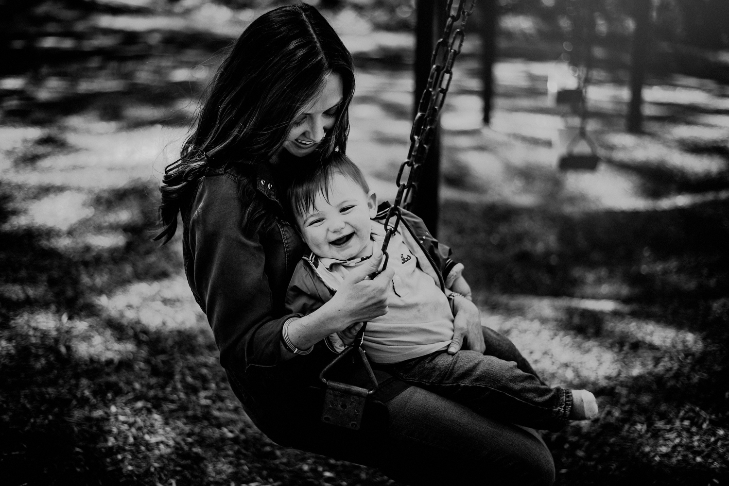 moment between mom and son on swingset in black and white photograph