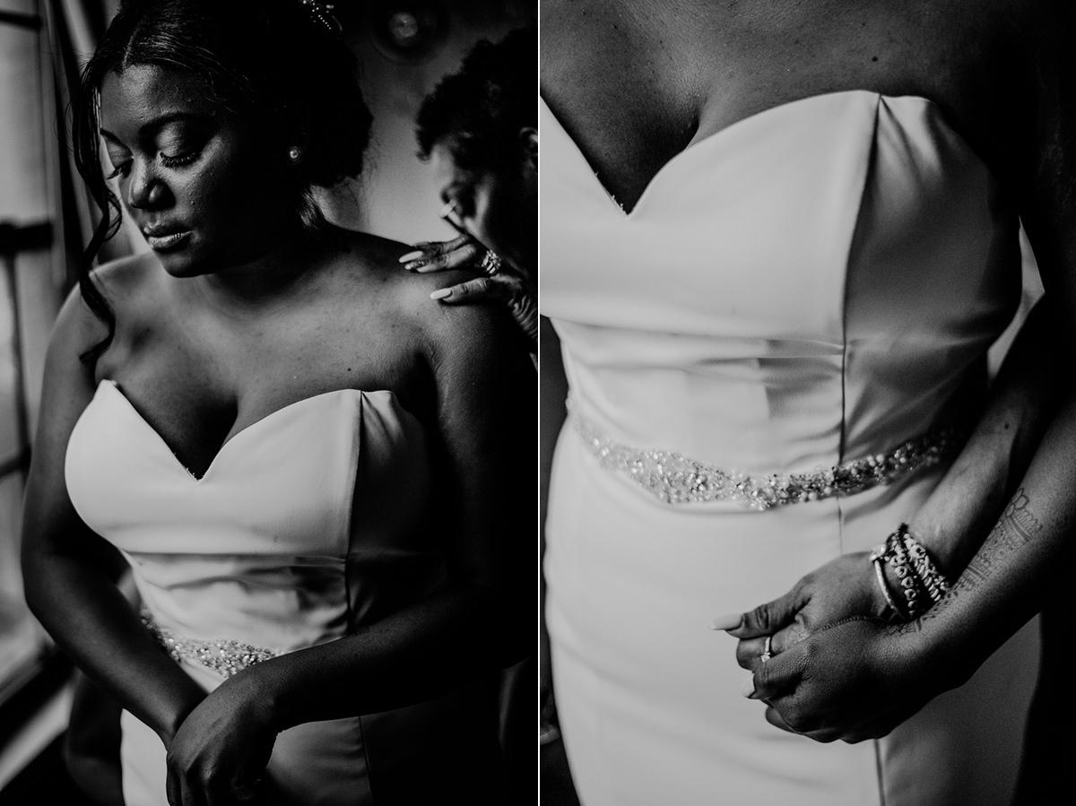 black and white photo of bride putting on wedding dress