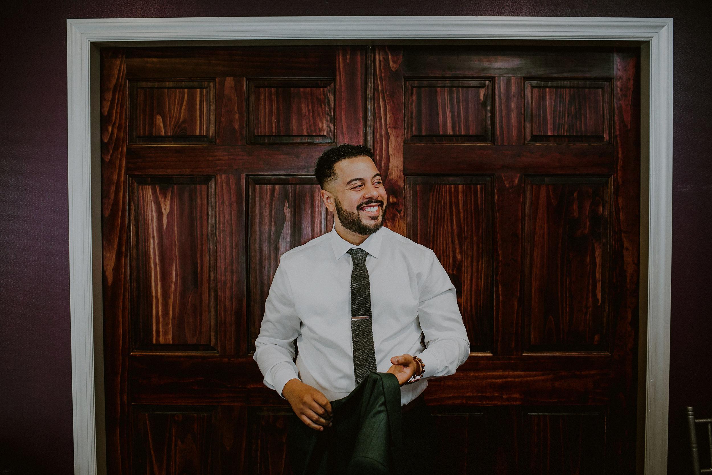 candid groom getting ready for wedding in woodbury ny