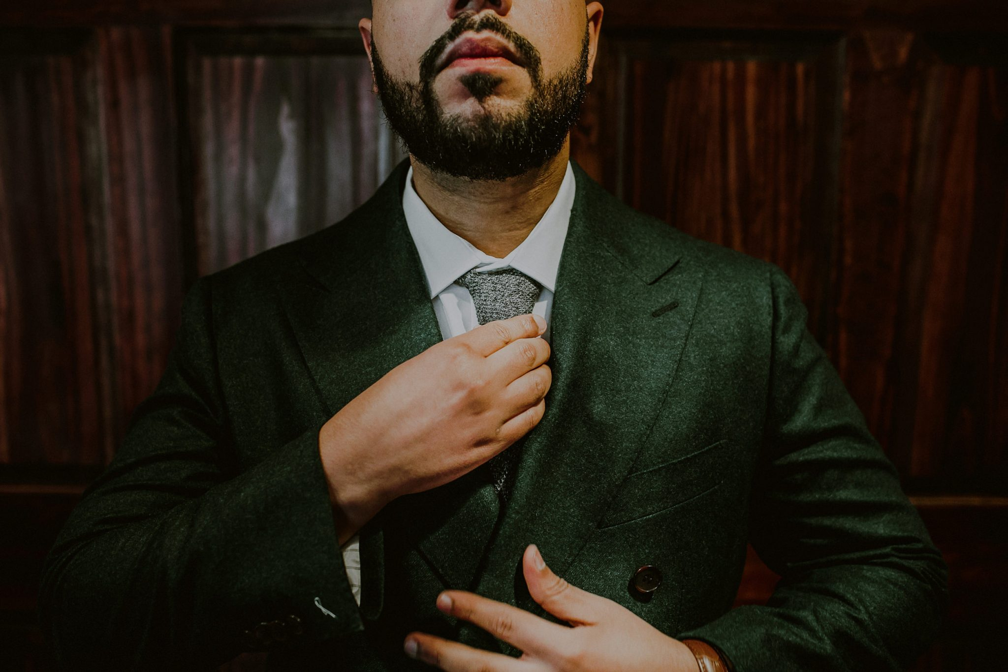 creative photo of well dressed groom in green suit preparing for wedding at fox hollow