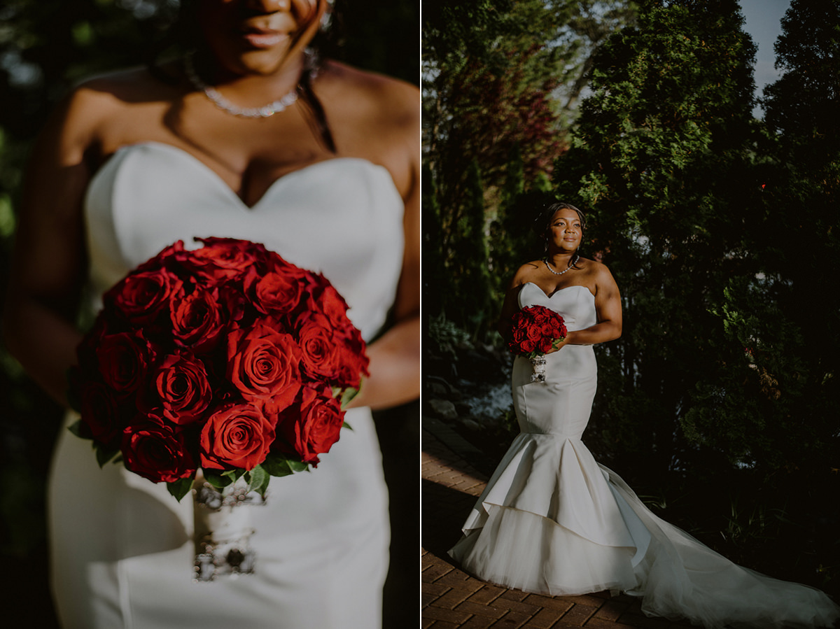 elegant bride posing in sunlight in fitted justin alexander dress and red flowers