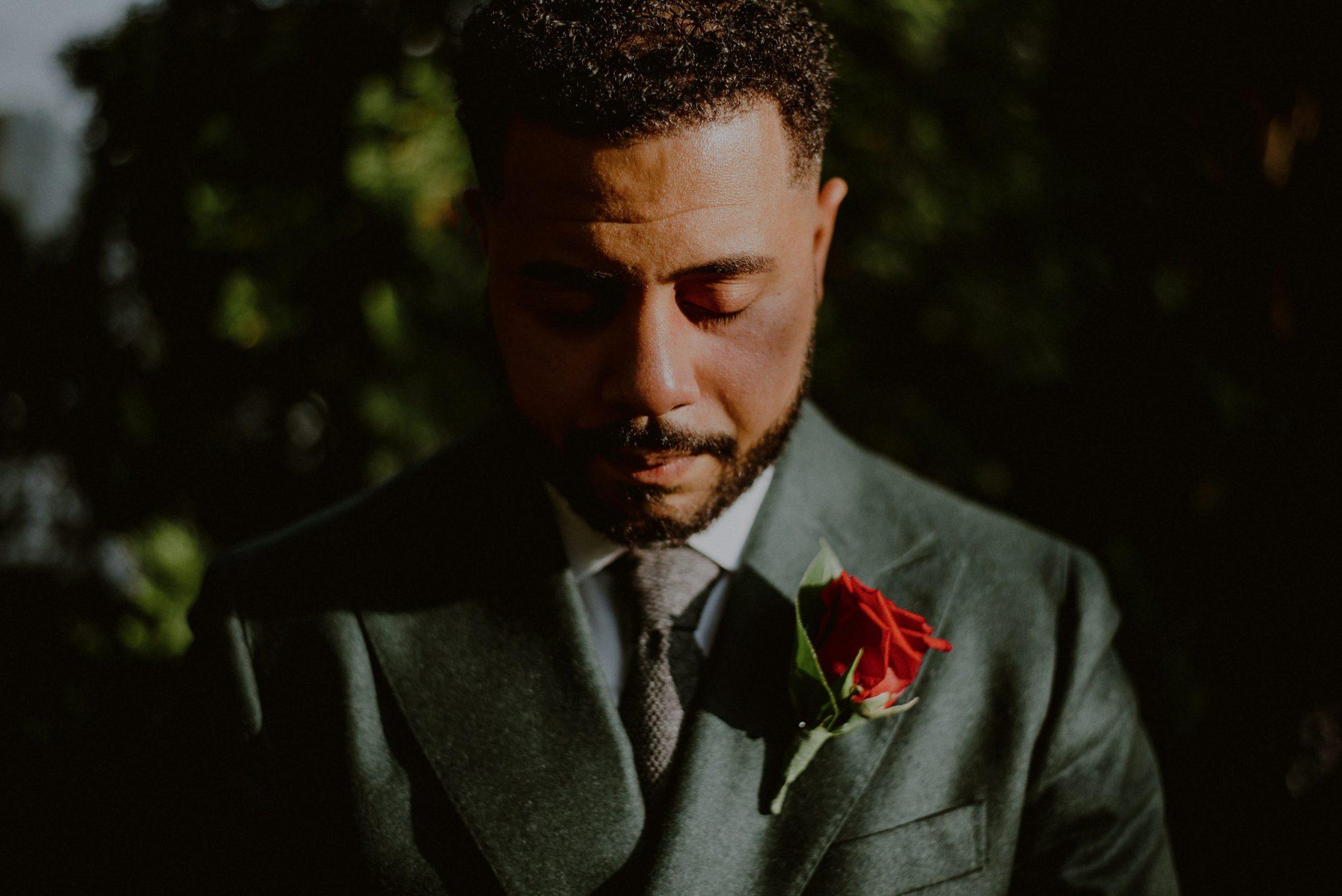 creative groom portrait in sunlight wearing green suit