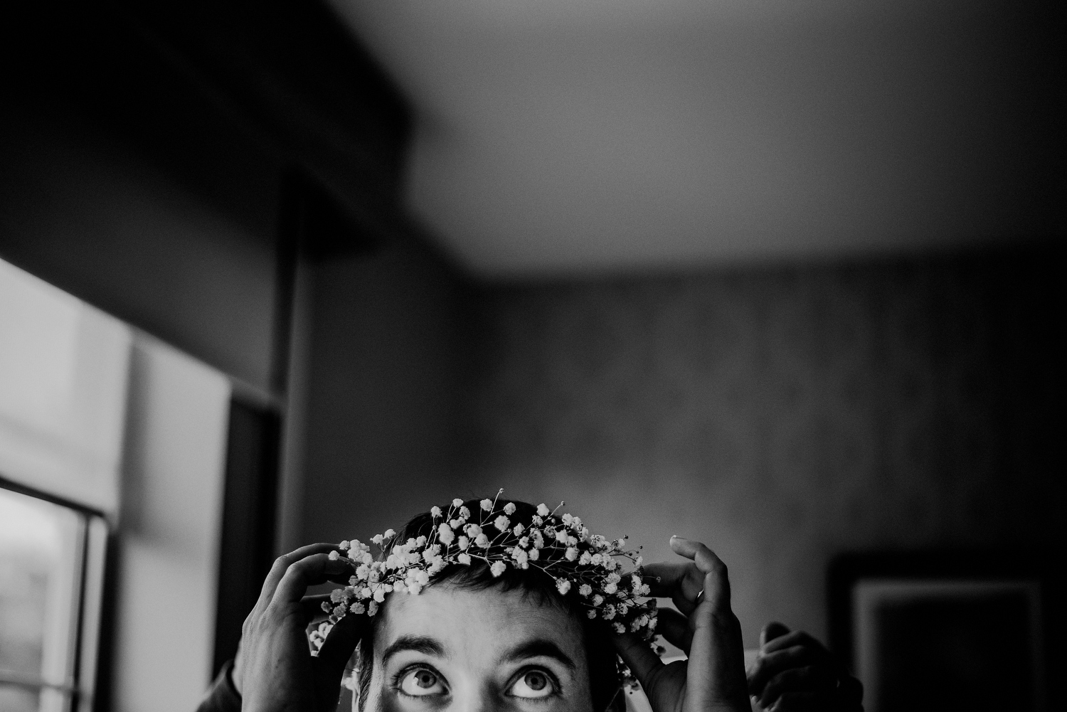 bride putting on flower crown for wedding