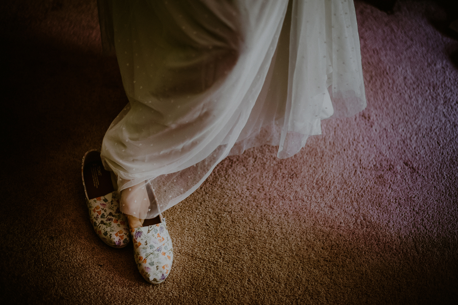 bride puts on toms wedding shoes
