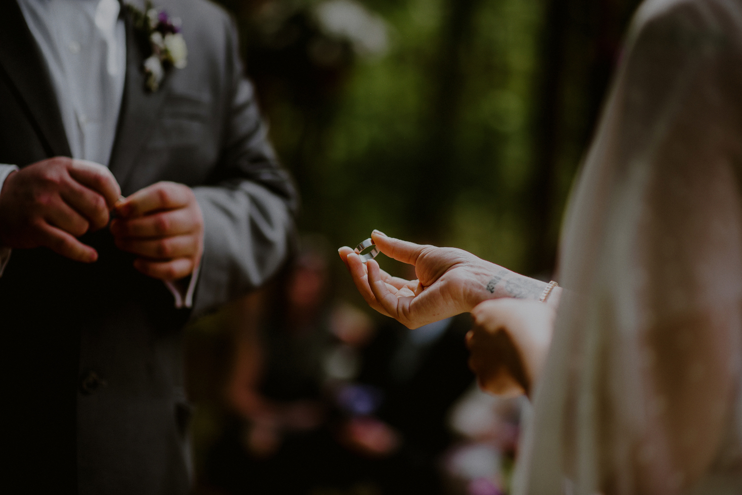 creative wedding photo of bride and groom putting on rings
