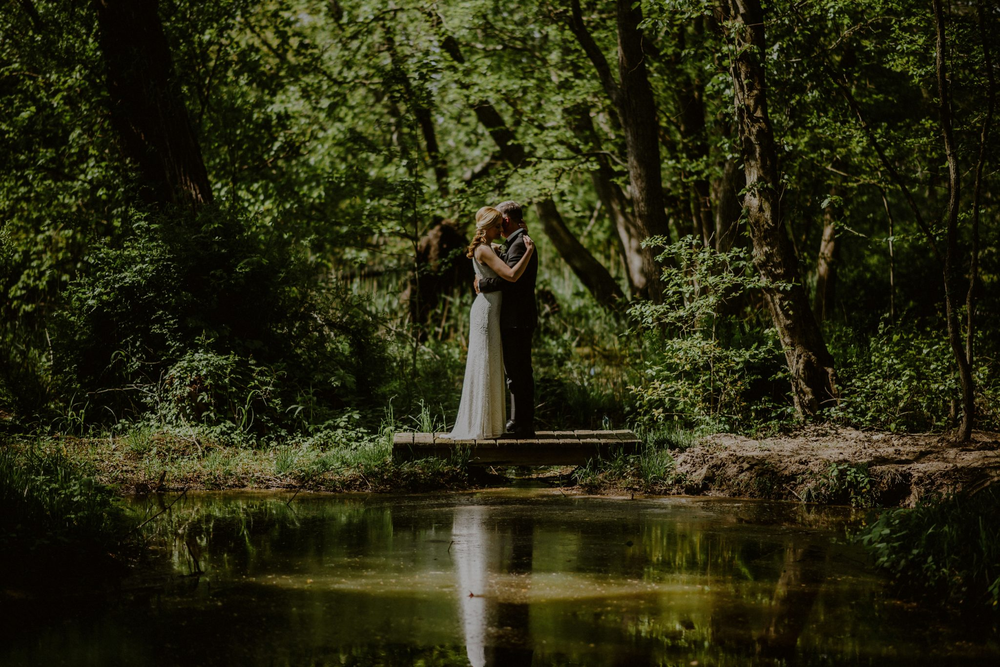 artistic wedding portrait of bride and groom with reflection