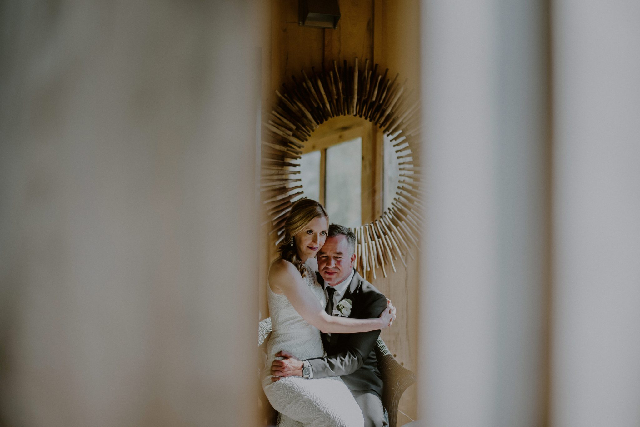 bride and groom snuggle during candid moment before ceremony